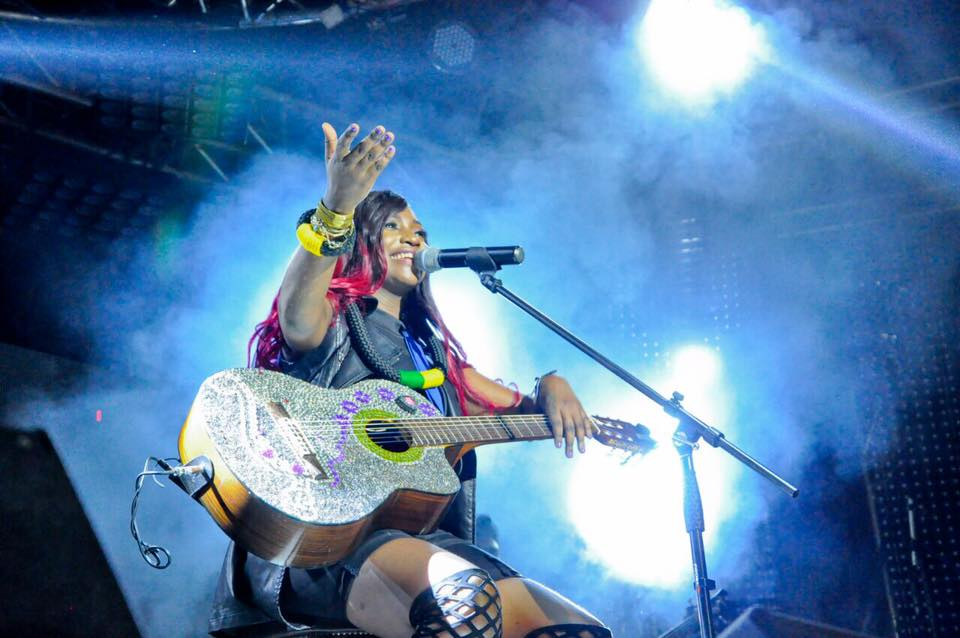 Ntale plucks the guitar.
