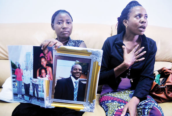The Late Ngobi's wife (R) and her sister, with a portrait of her husband who was executed in China.