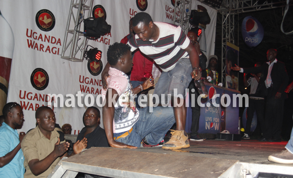 Leone Island's Producer Kays being helped back to his feet by Chameleone's international promoter Kinene after he fell during the scuffle with security.