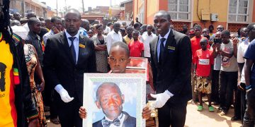 Bobi Wine's son Solomon Kampala leads the funeral procession with a portrait of his late grand father.