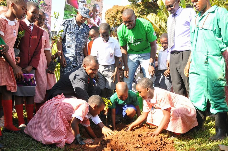 Minister Frank Mwebaze (in blue suit), Joseph Masembe (in green T-Shirt) and City Parents headmaster Joseph Isagara (in neck-tie) join join who were planting a tree.