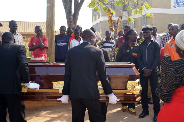 Bobi looks on as Uganda Uganda Funera; Services carries the casket containing the remains of his dad.