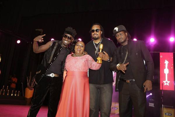 Joanita Kawalya accepts her Lifetime Achievement award from Bobi Wine, Navio and Bebe Cool.
