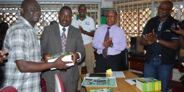 Dr Andrew Seguya ED Uganda Wild life Authority hands over books to Mr Wilson Adriko Librarian MUST as Dean of students Emmanuel Kyagaba and Mr Charly.