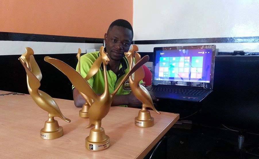 Filmmaker Joseph Ssebagala with the multiple awards he bagged at 2015's Uganda Film Festival.