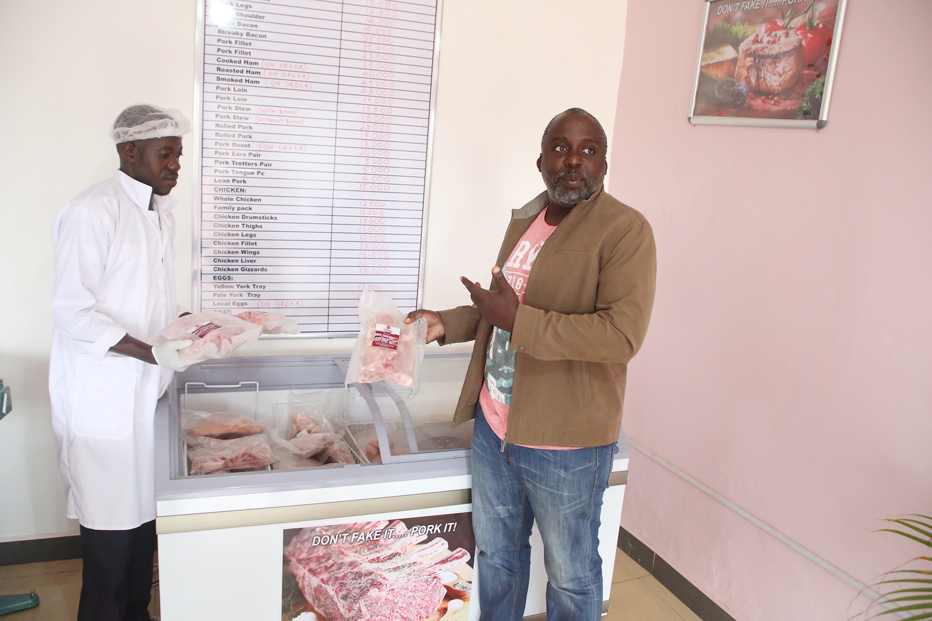 Jack Seruwo (R) and a Pork Packers staff display some of their products.