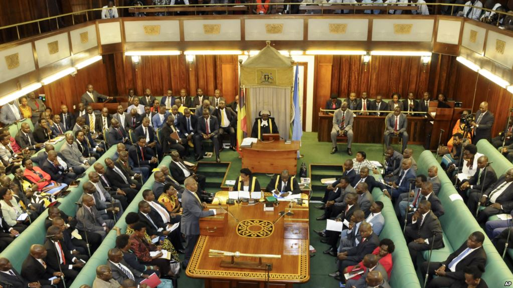 Uganda's Prime Minister, standing center-left, addresses Members of Parliament in Kampala, Uganda Thursday, Sept. 21, 2017. Ugandan police on Thursday fired tear gas to disperse protesters and arrested dozens of people opposed to plans to introduce legislation that could allow the longtime president Yoweri Museveni to extend his rule. (AP Photo/Ronald Kabuubi)