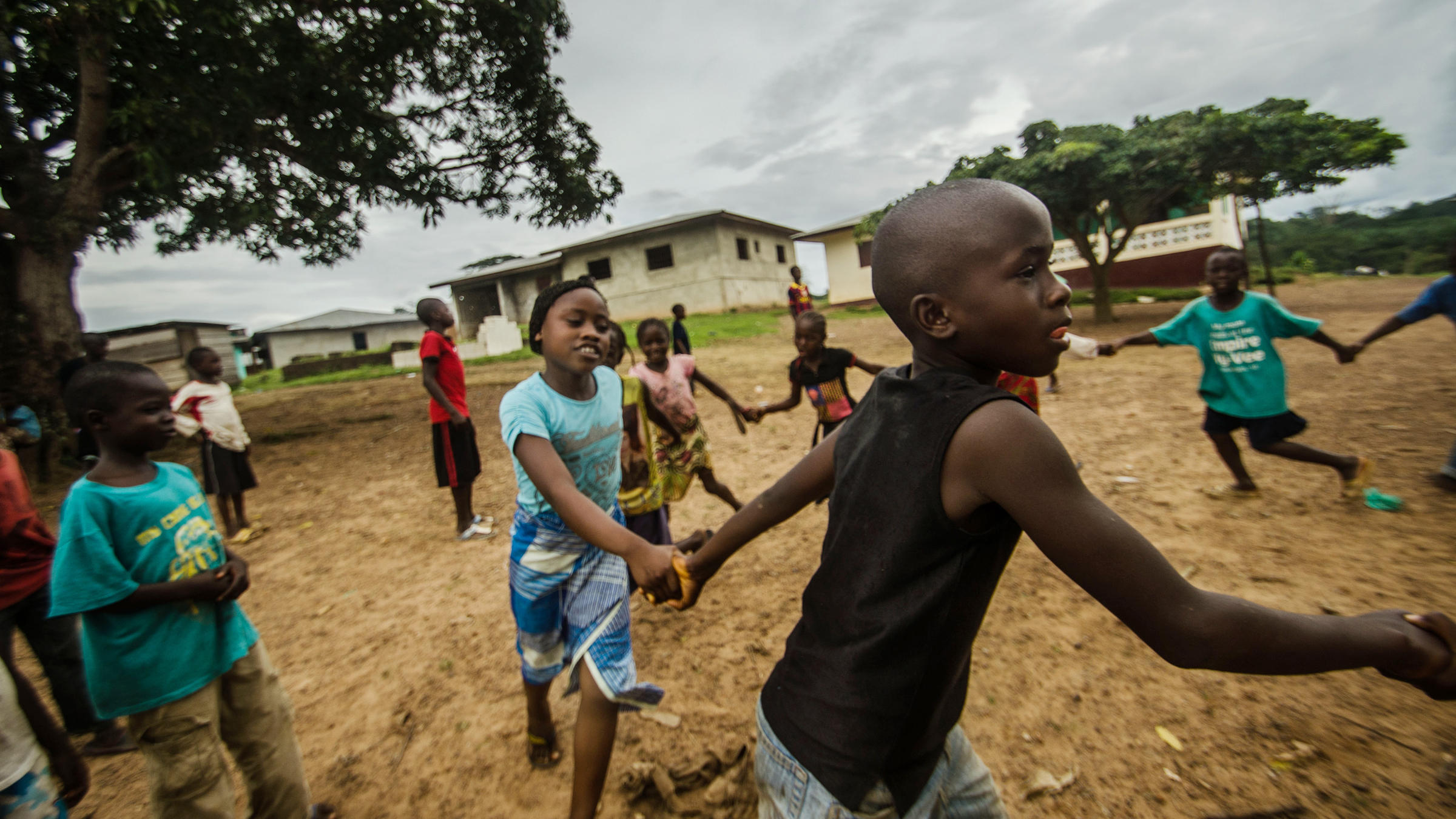Mariama and Fomba Kanneh play in an open space in Barkedu, Liberia. With schools closed across the country, many kids spend their time playing outside every day